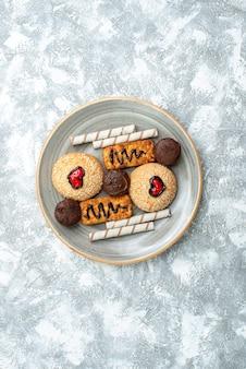 Bovenaanzicht zoete koekjes in plaat op witte achtergrond cookie biscuit suiker cake zoete taart cake