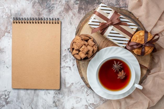 Bovenaanzicht zoete koekjes met cadeautje en kopje thee op de lichttafel
