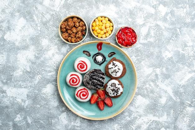 Bovenaanzicht zoete koekjes met chocoladetaart en snoepjes op witte achtergrond candy sugar biscuit cake zoete thee