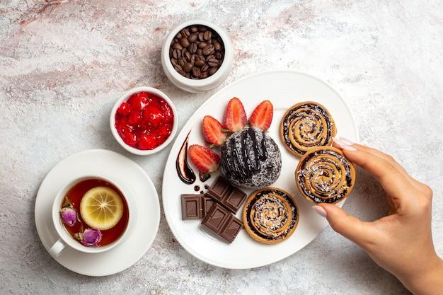 Bovenaanzicht zoete koekjes met chocoladetaart en thee op witte achtergrond koekjeskoekje suikerthee zoete cake
