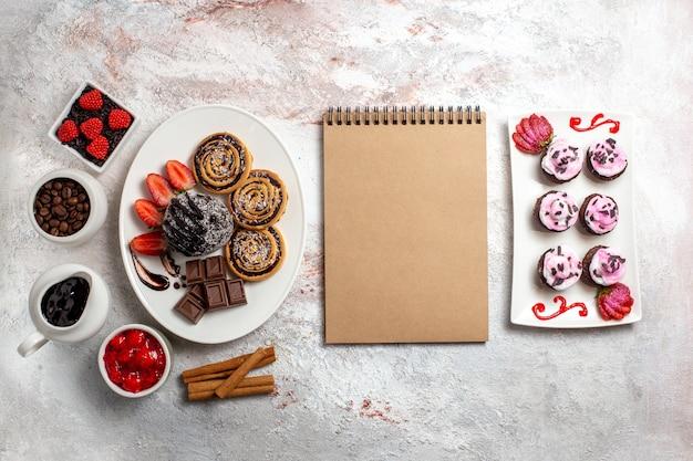 Bovenaanzicht zoete koekjes met chocoladetaart op witte achtergrond koekjeskoekje zoete cake suiker thee