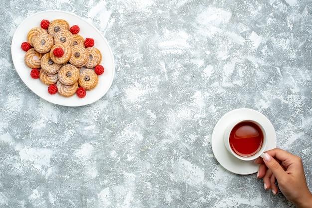 Bovenaanzicht zoete koekjes met frambozen confitures binnen plaat op witte achtergrond cookie suiker biscuit cake thee zoet