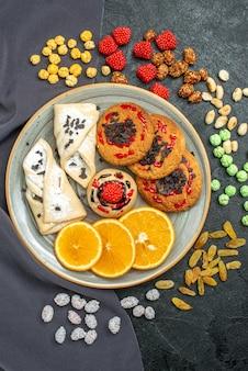 Bovenaanzicht zoete koekjes met gebak en sinaasappel op grijs oppervlak fruitkoekjeskoekje zoet