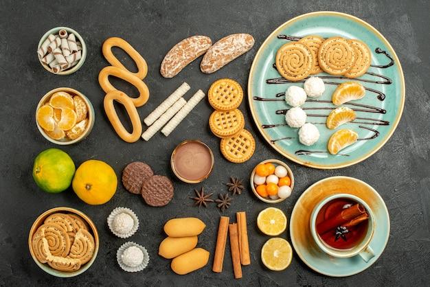 Bovenaanzicht zoete koekjes met koekjes en thee op grijze achtergrond
