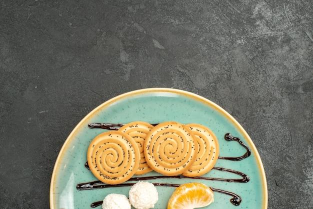 Bovenaanzicht zoete koekjes met kokos snoepjes in plaat op grijs bureau