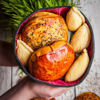 Bovenaanzicht zoete koekjes met qoqal en keta en shekerbura in menselijke hand