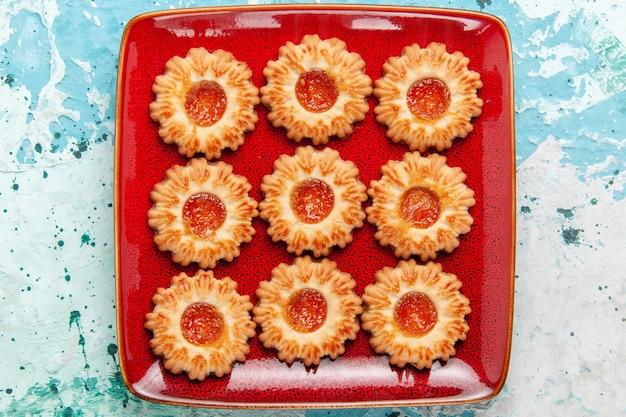 Bovenaanzicht zoete koekjes met sinaasappeljam in rode plaat op blauwe achtergrond