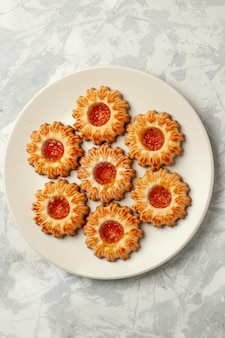 Bovenaanzicht zoete koekjes met sinaasappeljam op witte ondergrond