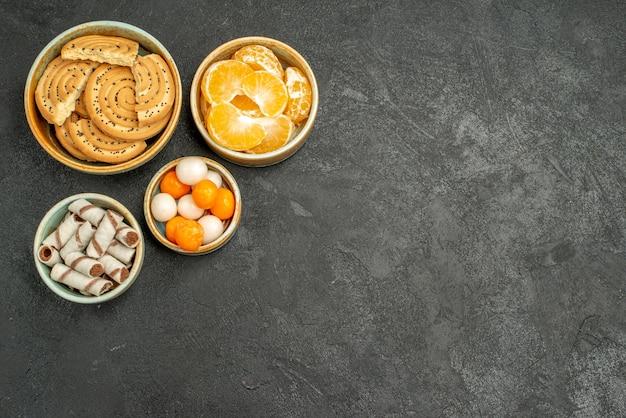 Bovenaanzicht zoete koekjes met snoepjes en mandarijnen op het grijze bureau