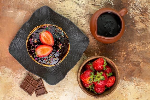 Bovenaanzicht zoete pannenkoeken met aardbeien op houten bureau