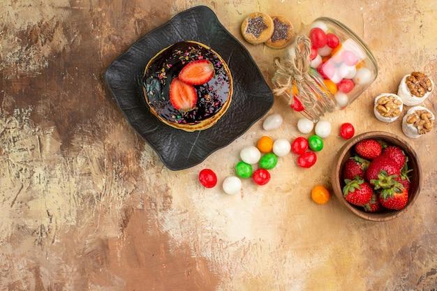 Bovenaanzicht zoete pannenkoeken met kleurrijke snoepjes op houten bureau