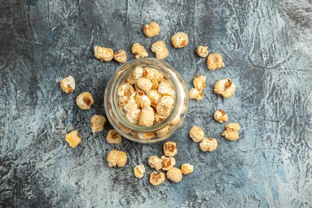 Bovenaanzicht zoete popcorn in glas kan op lichte ondergrond