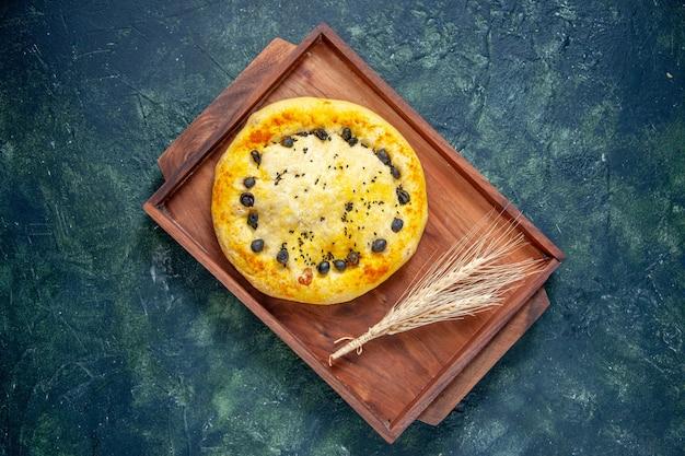 Bovenaanzicht zoete taart in houten bureau op donkerblauwe achtergrond hotcake fruit bak taart taart cookie dessert gebak bak