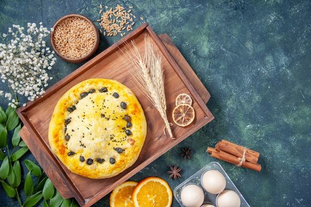 Bovenaanzicht zoete taart in houten bureau op een donkerblauwe achtergrond hotcake fruit bak cake cookie dessert gebak bak taart