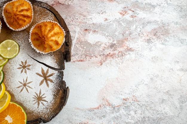 Bovenaanzicht zoete taarten met schijfjes citroen op wit bureau