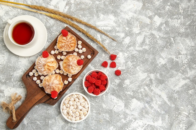Bovenaanzicht zoete taarten met snoepjes en kopje thee op lichte witte achtergrond