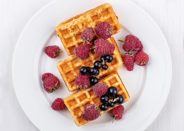 Bovenaanzicht zoete wafels op een bord met frambozen en zwarte bessen
