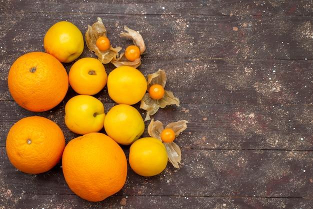 Bovenaanzicht zoete zachte abrikozen oranje gekleurd met sinaasappels en physalises heerlijk zomerfruit op de bruine achtergrond cake fruit vers foto