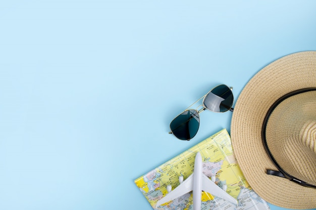 Bovenaanzicht zonnebril en een hoed met een kaart op de blauwe achtergrond