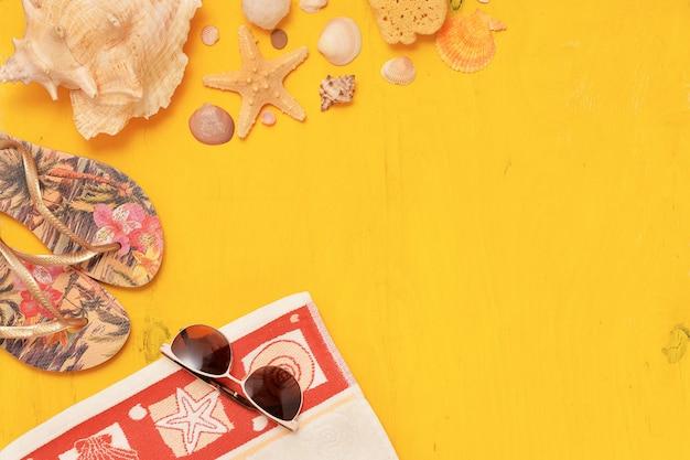 Bovenaanzicht zonnebril, handdoek, schelpen en slippers