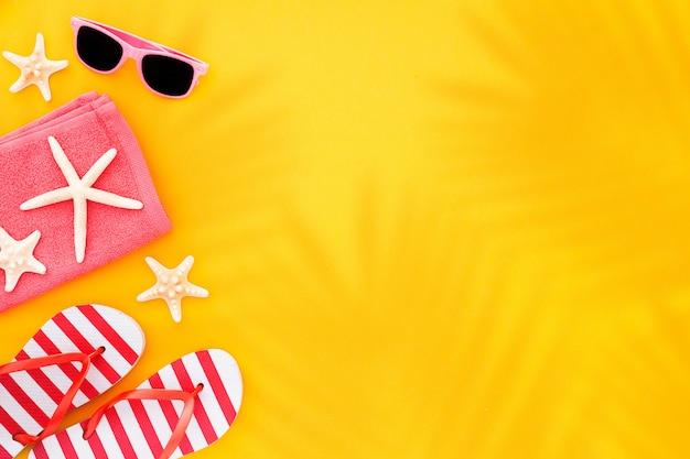 Bovenaanzicht zonnebrillen, handdoek zeester en flip flops, op geel met zonlicht en schaduw van palmbladeren.