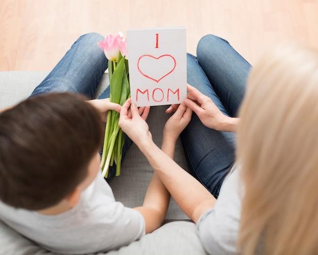 Bovenaanzicht zoon verrassende moeder met bloemen en kaart