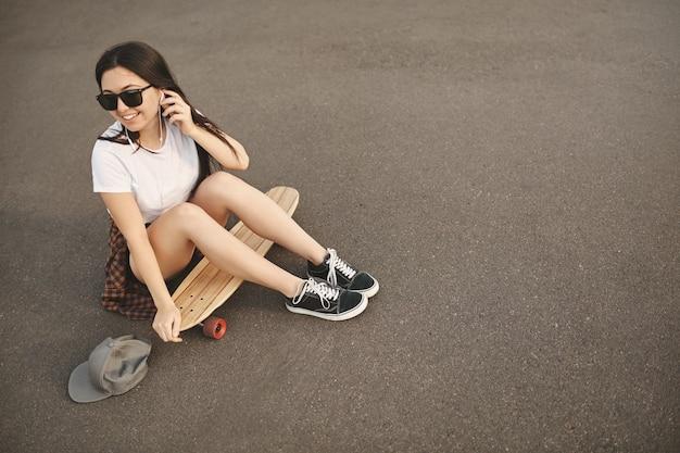 Bovenaanzicht zorgeloze hipster meisje in zonnebril, snapback op de grond