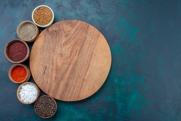 Bovenaanzicht zout en peper met andere kruiden op het donkerblauwe peperbureau van het oppervlakte-ingrediënt