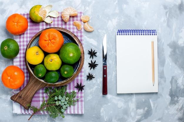 Bovenaanzicht zure verse mandarijnen met citroenen en notitieblok op wit bureau