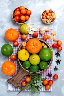 Bovenaanzicht zure verse mandarijnen met citroenen en pruimen op het lichtwitte bureau