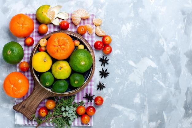 Bovenaanzicht zure verse mandarijnen met citroenen en pruimen op wit bureau