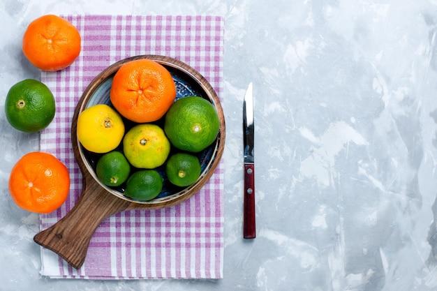 Bovenaanzicht zure verse mandarijnen met citroenen op het lichtwitte bureau