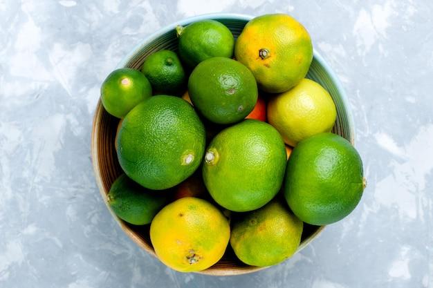 Bovenaanzicht zure verse mandarijnen met citroenen op licht wit oppervlak