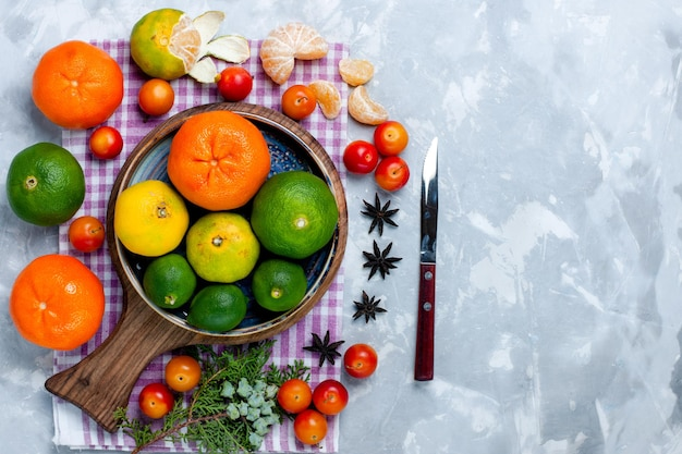 Bovenaanzicht zure verse mandarijnen met citroenen op wit bureau