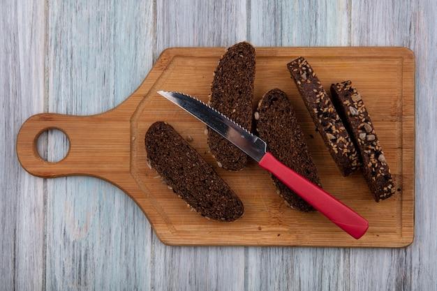 Bovenaanzicht zwart brood met mes op snijplank op grijze achtergrond
