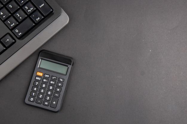 Bovenaanzicht zwart kantoor propt toetsenbord rekenmachine op donkere tafel kopieerruimte