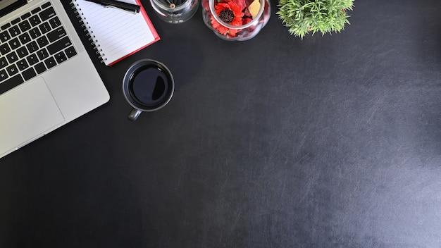 Bovenaanzicht zwart lederen tafel met laptop, kopje koffie en kantoorbenodigdheden.