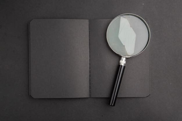 Bovenaanzicht zwart notebook vergrootglas op donkere tafel