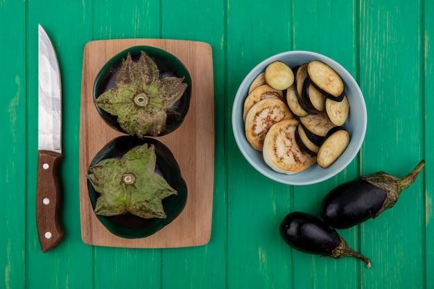 Bovenaanzicht zwarte aubergine met een mes op een snijplank op een groene achtergrond