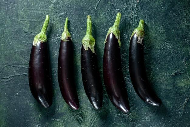 Bovenaanzicht zwarte aubergine op een donkere ondergrond groente verse maaltijd salade voedsel peper kleur rijp