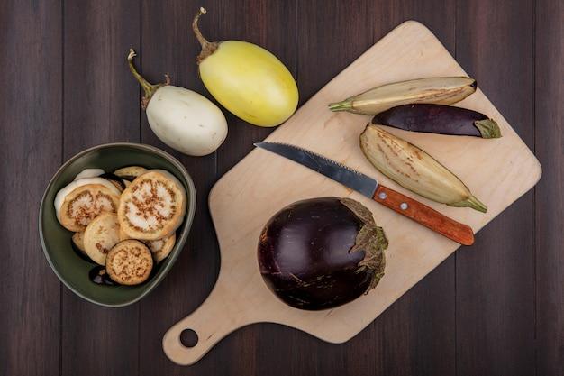 Bovenaanzicht zwarte aubergine op snijplank met mes en plakjes in kom op houten achtergrond