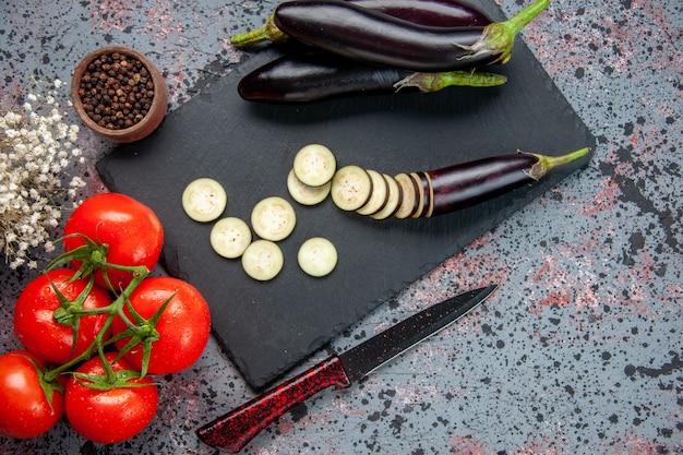 Bovenaanzicht zwarte aubergines met verse rode tomaten op blauw oppervlak groeien voedsel diner boom kleur maaltijd salade foto