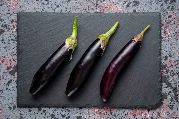 Bovenaanzicht zwarte aubergines op snijplank blauwe oppervlakte lunch salade rijp kleur maaltijd eten