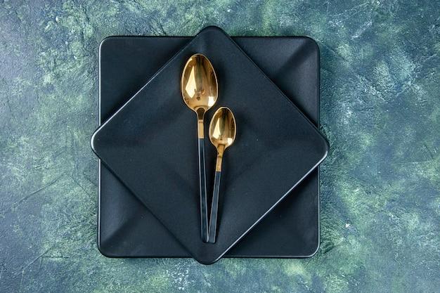 Bovenaanzicht zwarte borden met gouden lepels op donkere ondergrond kleur eten restaurant diner keuken café