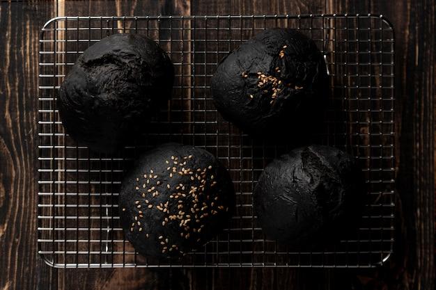 Bovenaanzicht zwarte bugrer broodjes op dienblad