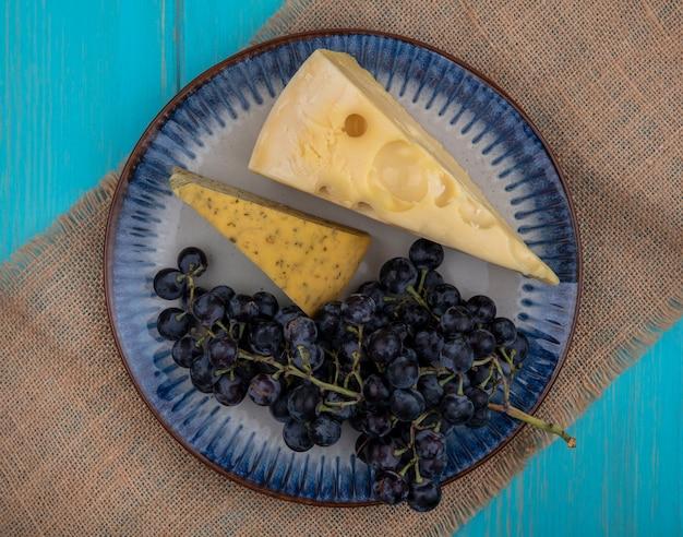 Bovenaanzicht zwarte druiven met plakjes kaas op een plaat op een beige servet
