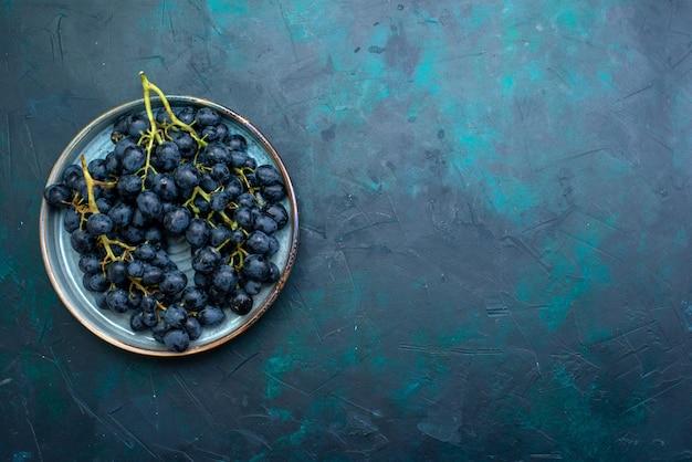 Bovenaanzicht zwarte druiven op donkerblauw