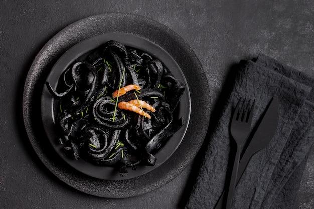 Bovenaanzicht zwarte garnalen pasta en zwart bestek