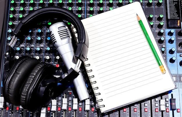 Bovenaanzicht zwarte hoofdtelefoon, sliver retro vintage microfoon en notebook op console soundboard mixer