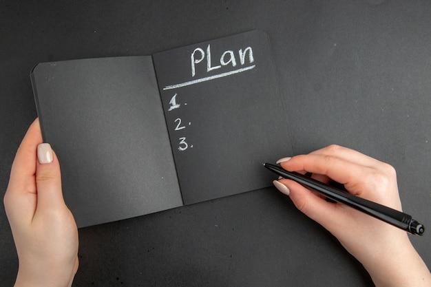 Bovenaanzicht zwarte notebook en pen in vrouwelijke hand op zwarte ondergrond